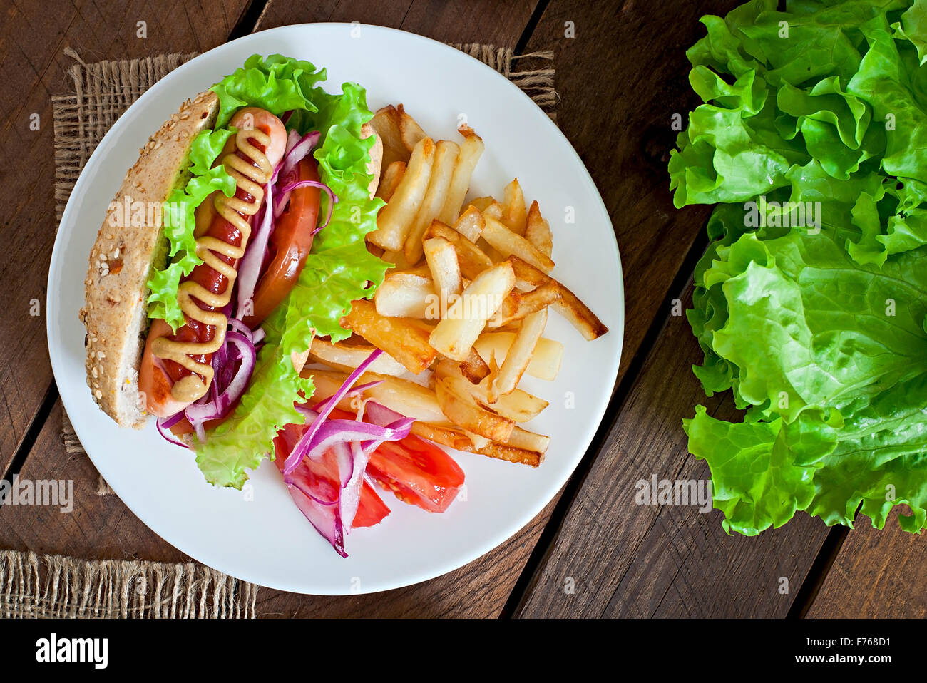 Hot Dogs - sandwich with French fries on white plate, close-up. - Stock Image