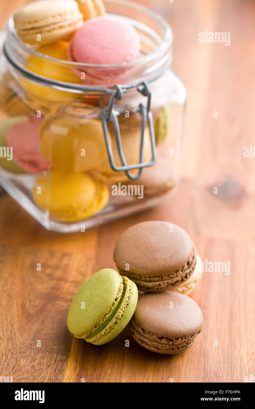 tasty colorful macarons in jar on wooden table - Stock Image