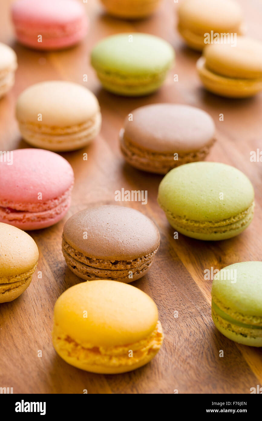 tasty colorful macarons on wooden table - Stock Image