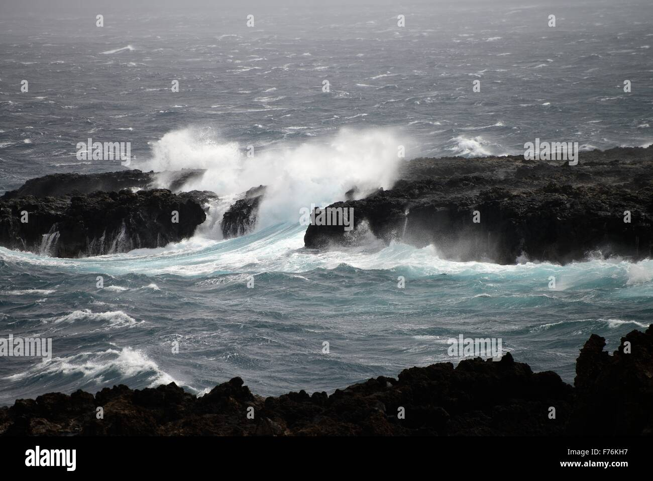 wave breaking rock - Stock Image