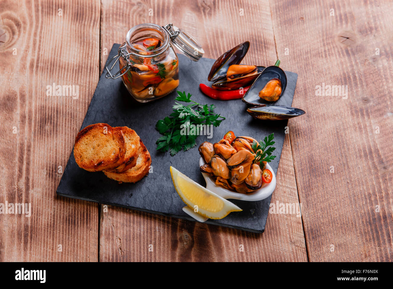 Marinated mussels with lemon and croutons - Stock Image