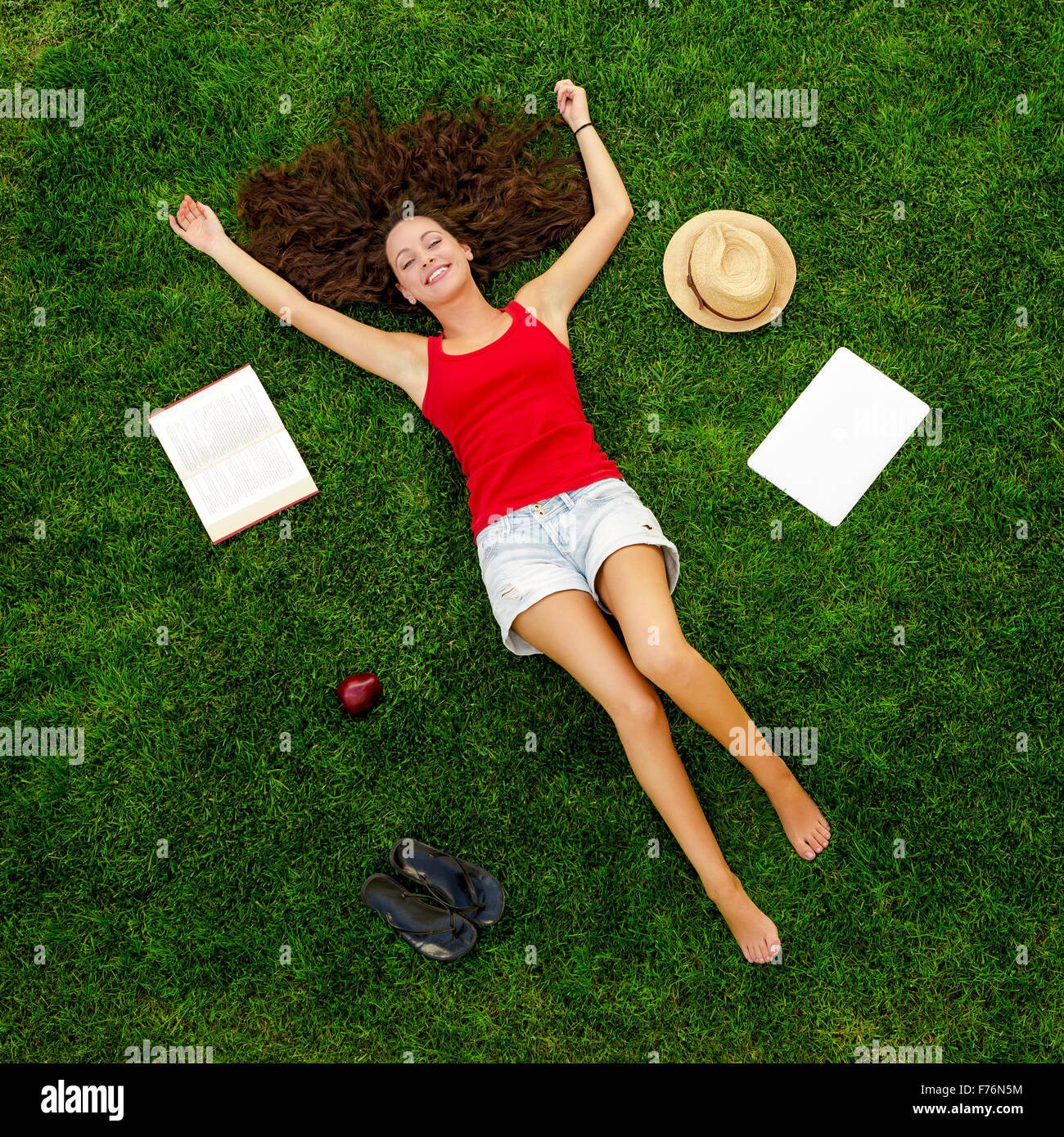 Beautiful and happy young woman lying on the grass - Stock Image