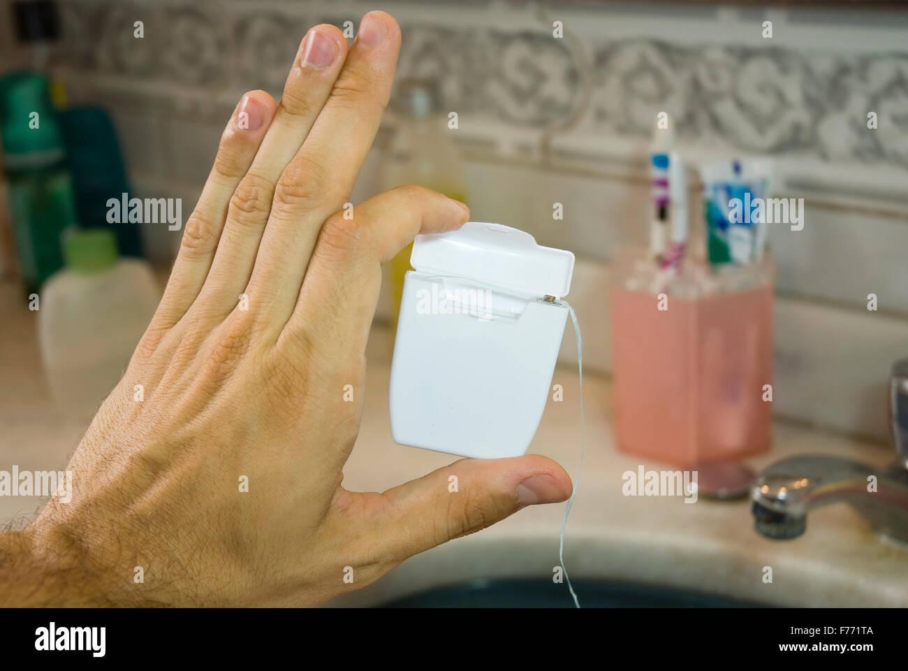Hand holding dental floss box - Stock Image