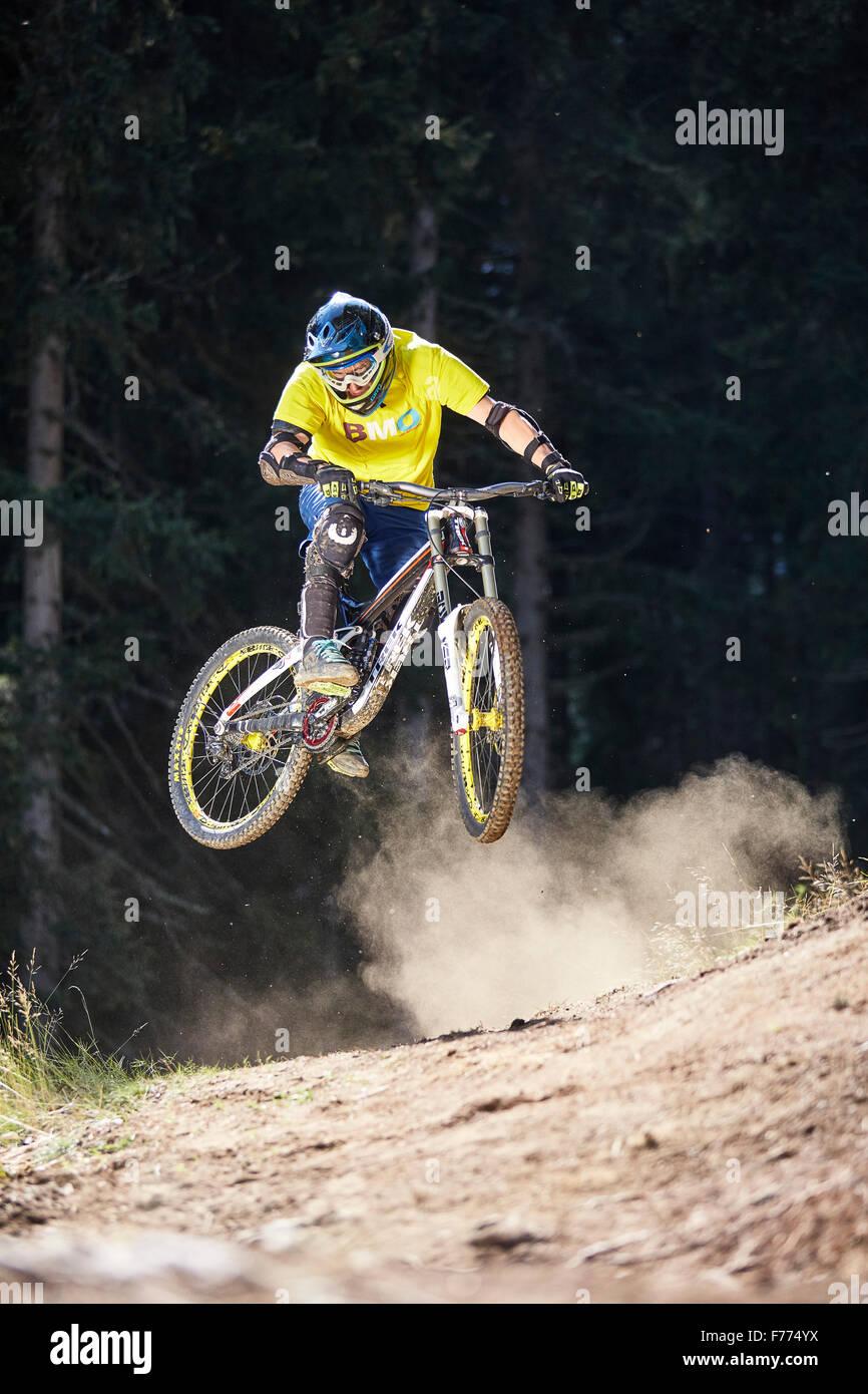 Mountain bikers, downhill biker jumping on a downhill trail, Mutterer Alm, Muttereralmpark, Mutters, Innsbruck, - Stock Image