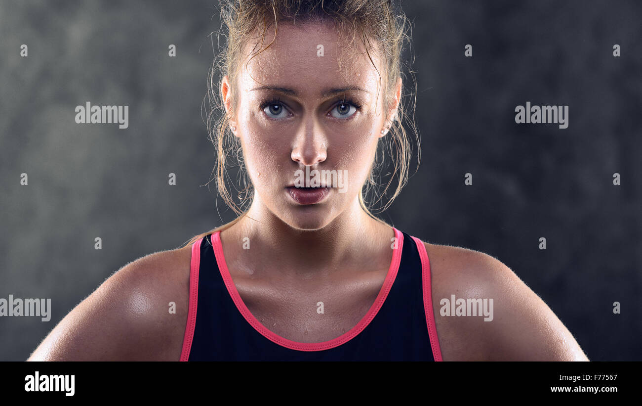 Head and Shoulders Portrait of a sweating Athletic Blond Woman Wearing Pink and Black Tank Top and Standing with - Stock Image
