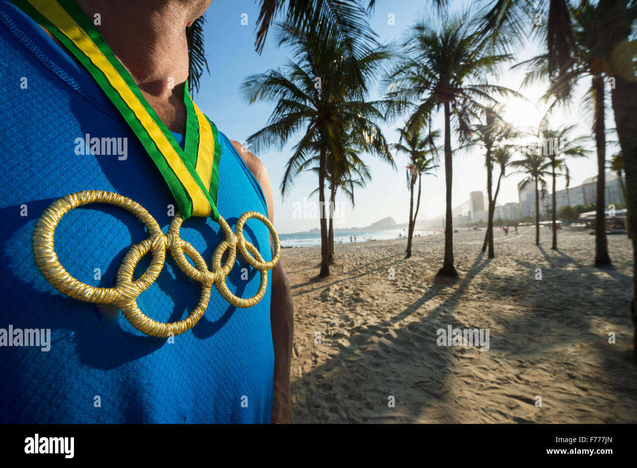 RIO DE JANEIRO, BRAZIL - OCTOBER 30, 2015: Athlete wearing Olympic rings gold medal stands in front of a sunset - Stock Image