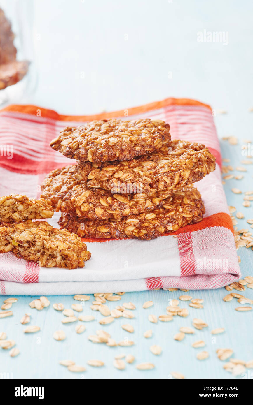 Homemade oatmeal banana cookies resting on napkin surrounded by oatmeal, jar and blu wooden table - Stock Image