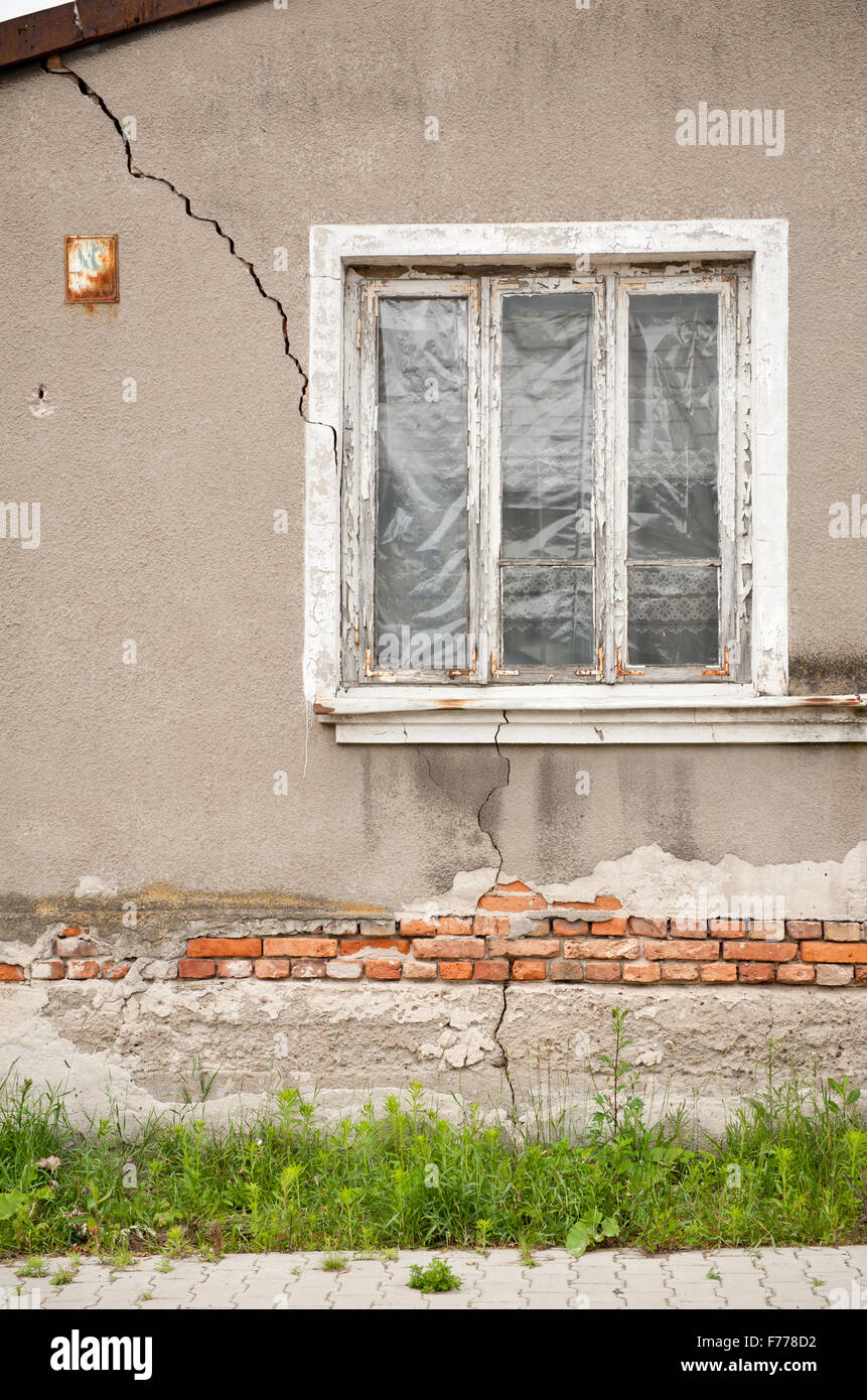 Decrepit house cracked wall and fissure, old abandoned home with foil in window and crevice in whole side, damaged - Stock Image