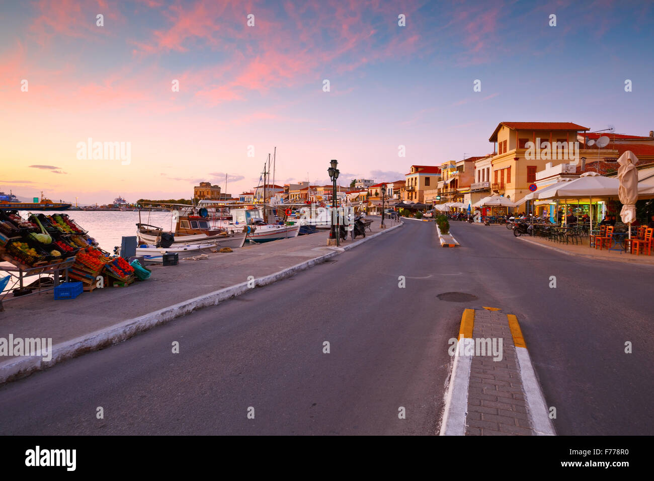 View of the seafront with coffee shops, bars and restaurants and fishing boats in the harbour of Aegina island, - Stock Image