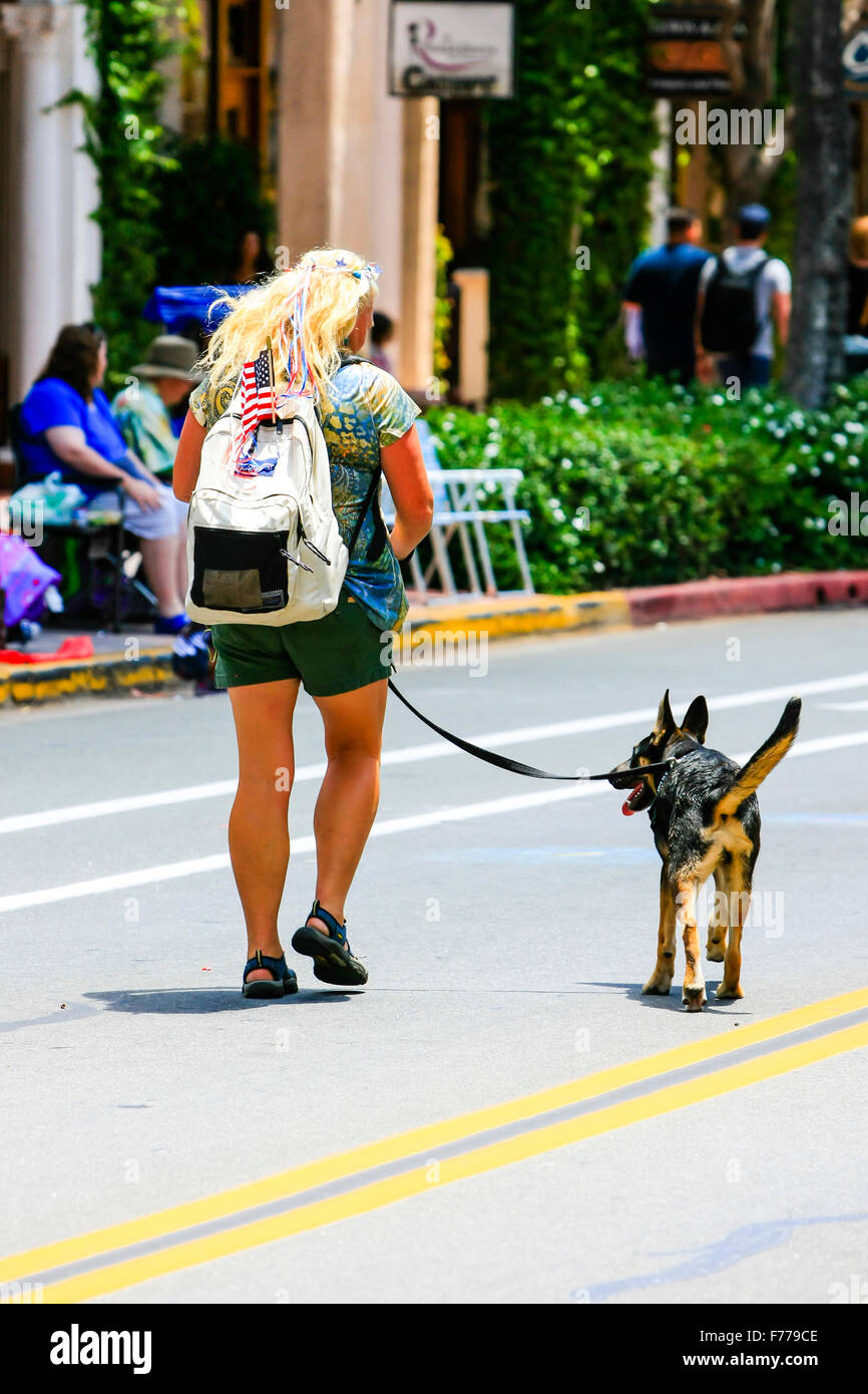 Blond haired woman taking her dog for a walk down the middle of the street in Santa Barbara California on July 4th - Stock Image