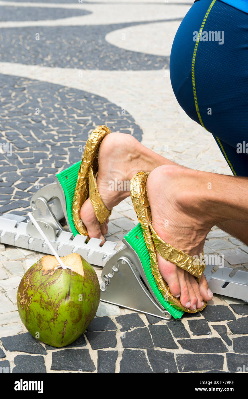 63184e56adfb8b Brazilian athlete wearing flip flops crouching at the start position in running  blocks with a coconut at Copacabana Beach