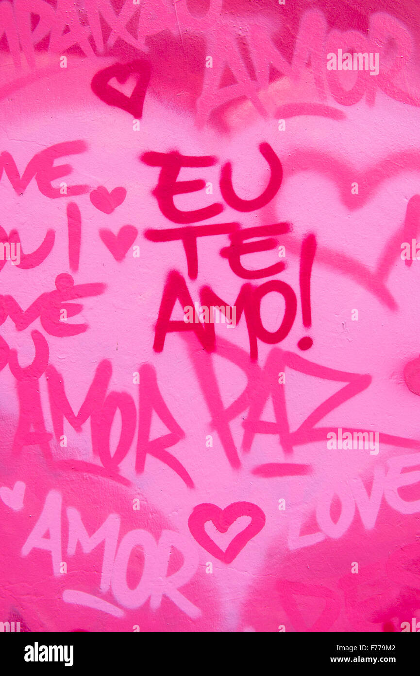 International love and peace graffiti in English and Brazilian Portuguese writing on pink wall in Rio de Janeiro, - Stock Image