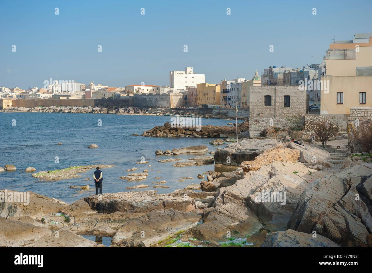 Trapani Sicily coast, a man stands alone on the north shore of the Trapani coastline, Sicily. - Stock Image
