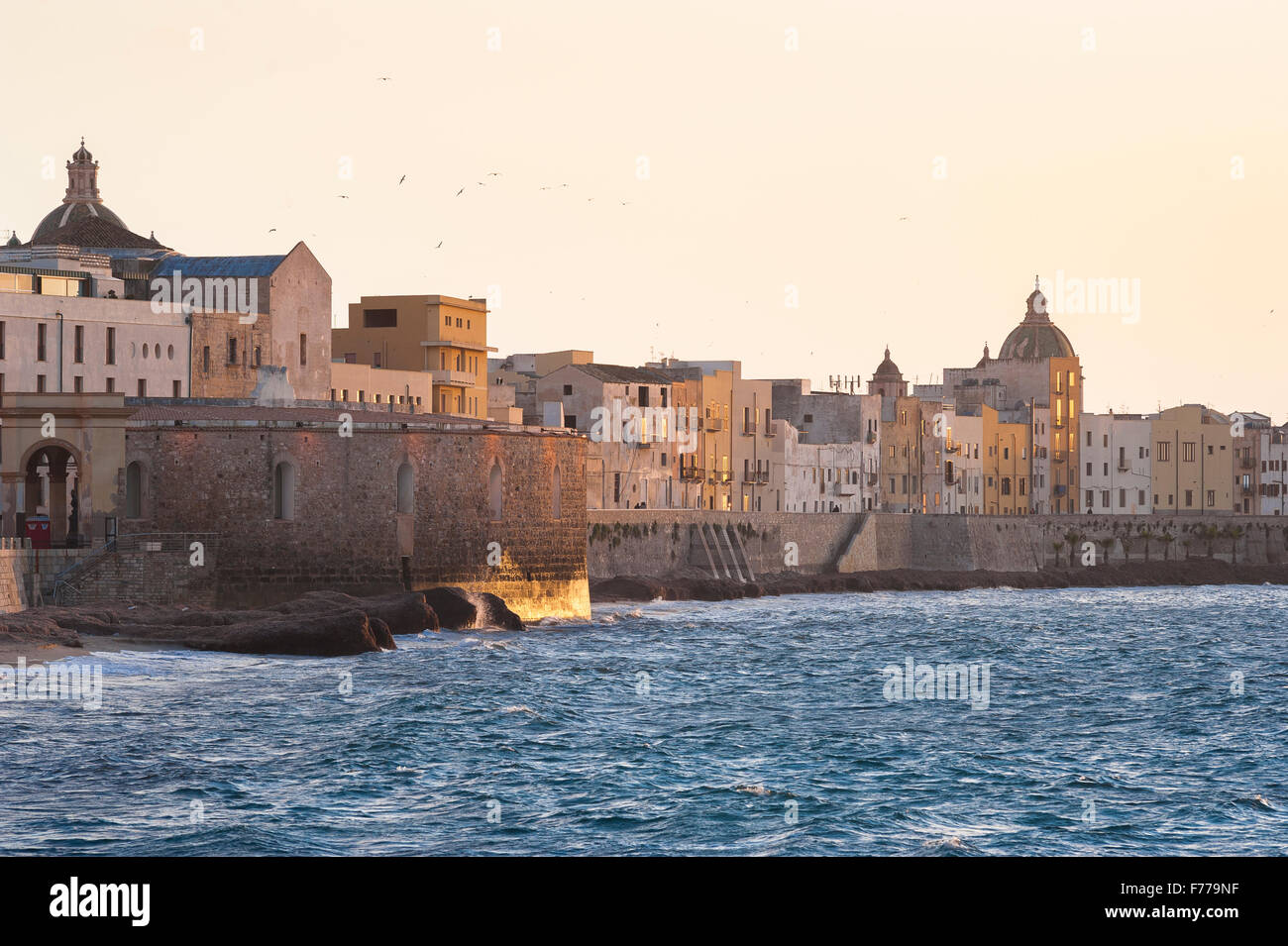 Trapani Sicily coast, the sea wall and skyline of the north side of Trapani at sunset, Sicily. - Stock Image