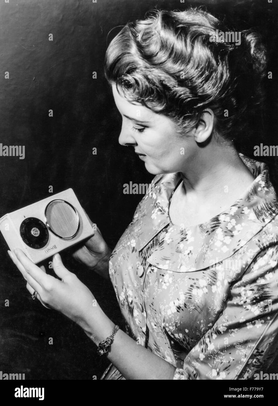 a woman with a powered by solar energy portable radio,1957 - Stock Image