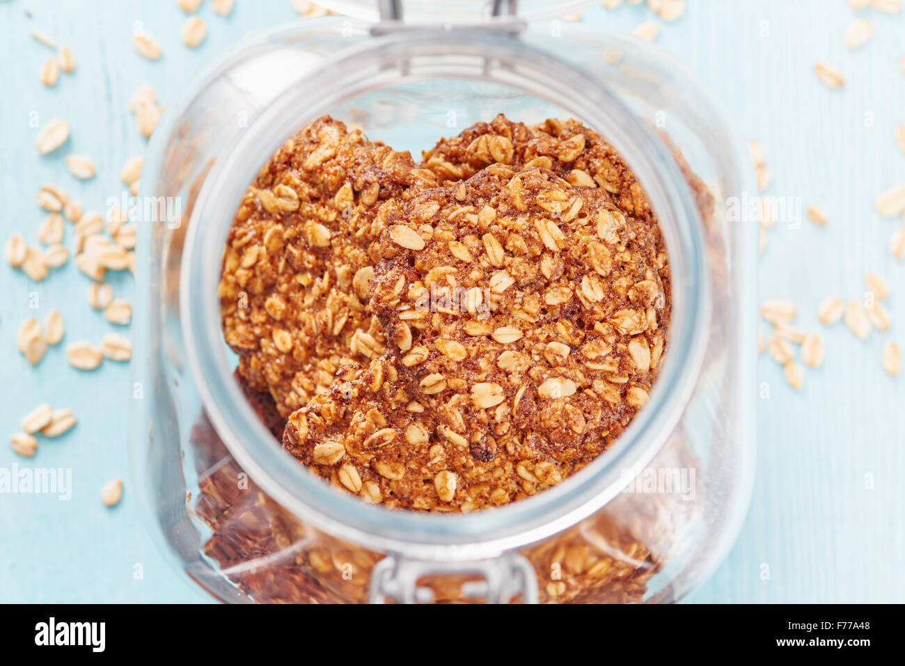 Homemade oatmeal banana cookies in the jar surrounded by oatmeal on blu wooden table - Stock Image