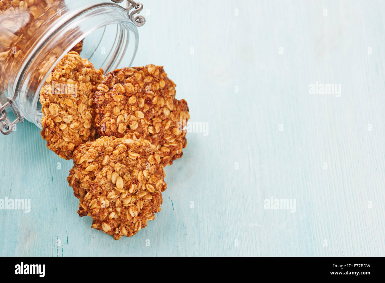 Homemade oatmeal banana cookies, jar and blu wooden table - Stock Image