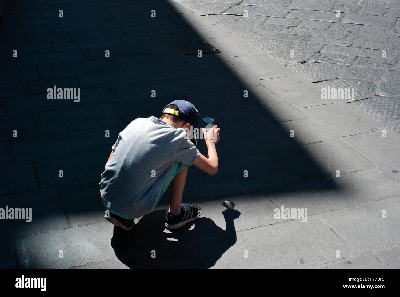 boy crouches on street Burning Paper Using Magnifying Glass - Stock Image