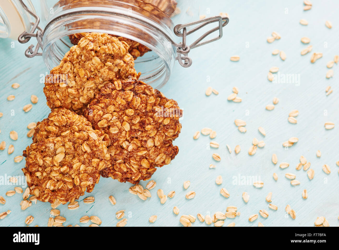 Homemade oatmeal banana cookies, surrounded by oatmeal, jar and blu wooden table - Stock Image