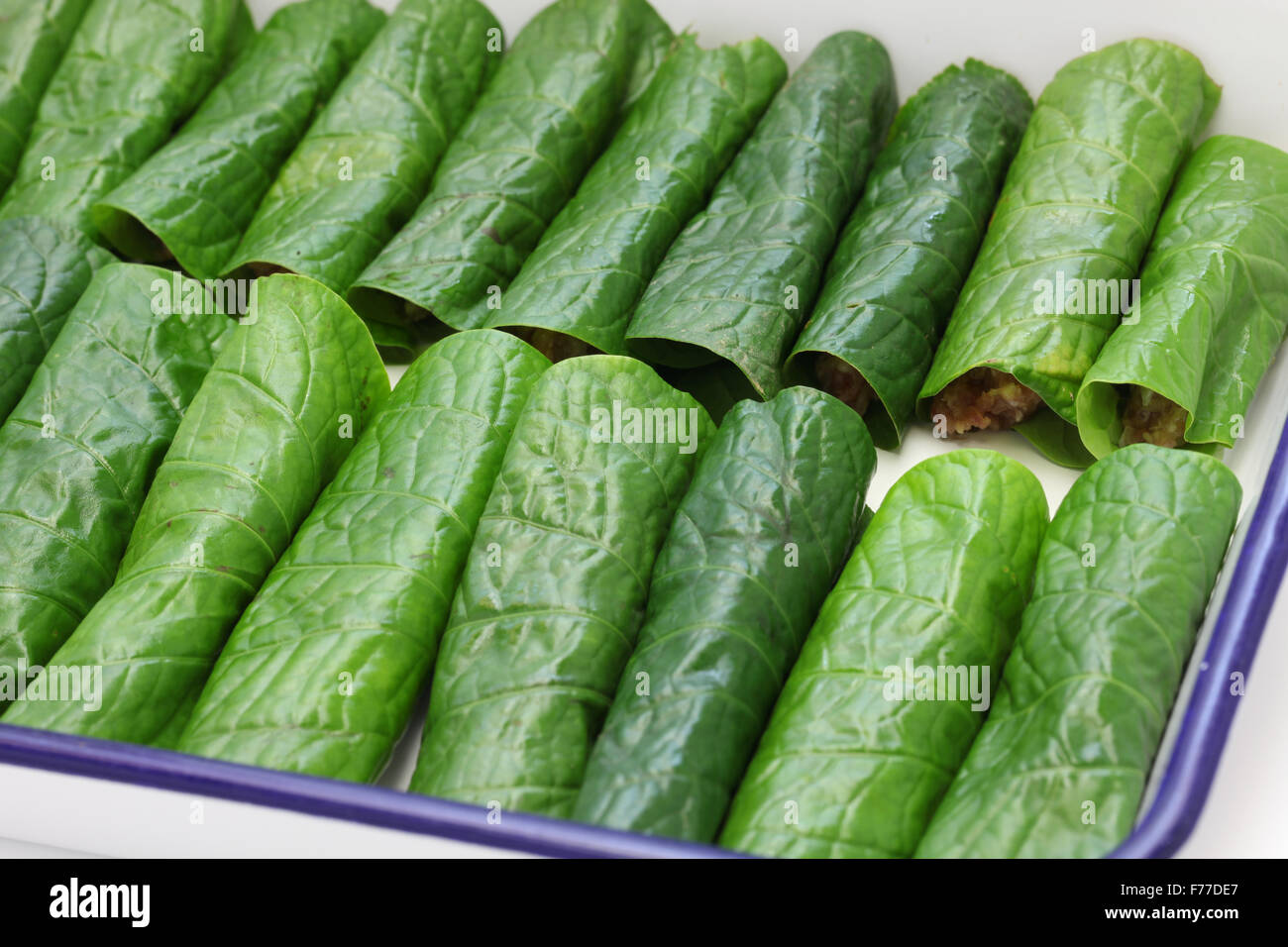 preparing bo la lot, vietnamese cuisine, grilled minced beef wrapped in betel leaf - Stock Image