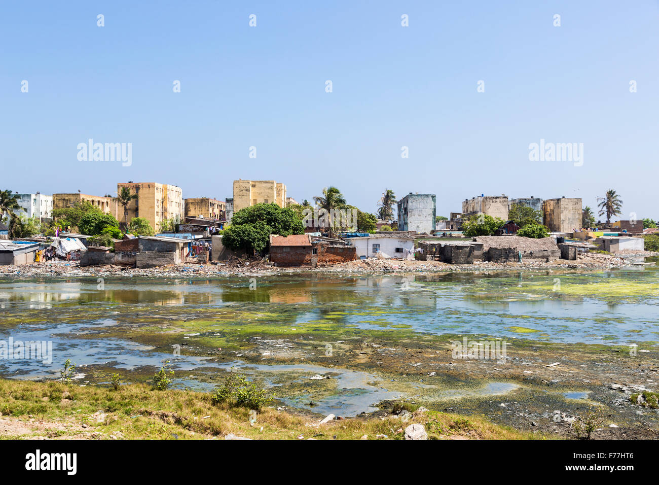 Third world poverty lifestyle: Apartment blocks, riverside shacks, slums on the banks of the polluted Adyar River - Stock Image