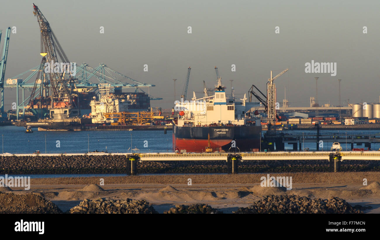 North Sea, on board ship arriving in Rotterdam harbour at sunrise with shipping, bulk containers tugs quayside cranes - Stock Image