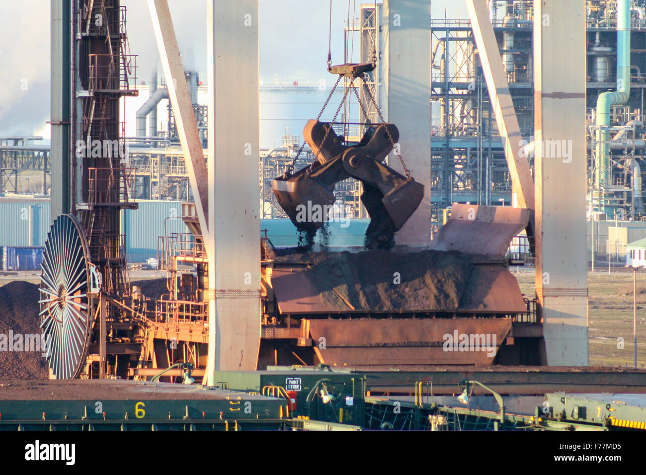 North Sea, on board ship arriving in Rotterdam harbour at sunrise with shipping, bulk cranes giant grab bucket - Stock Image