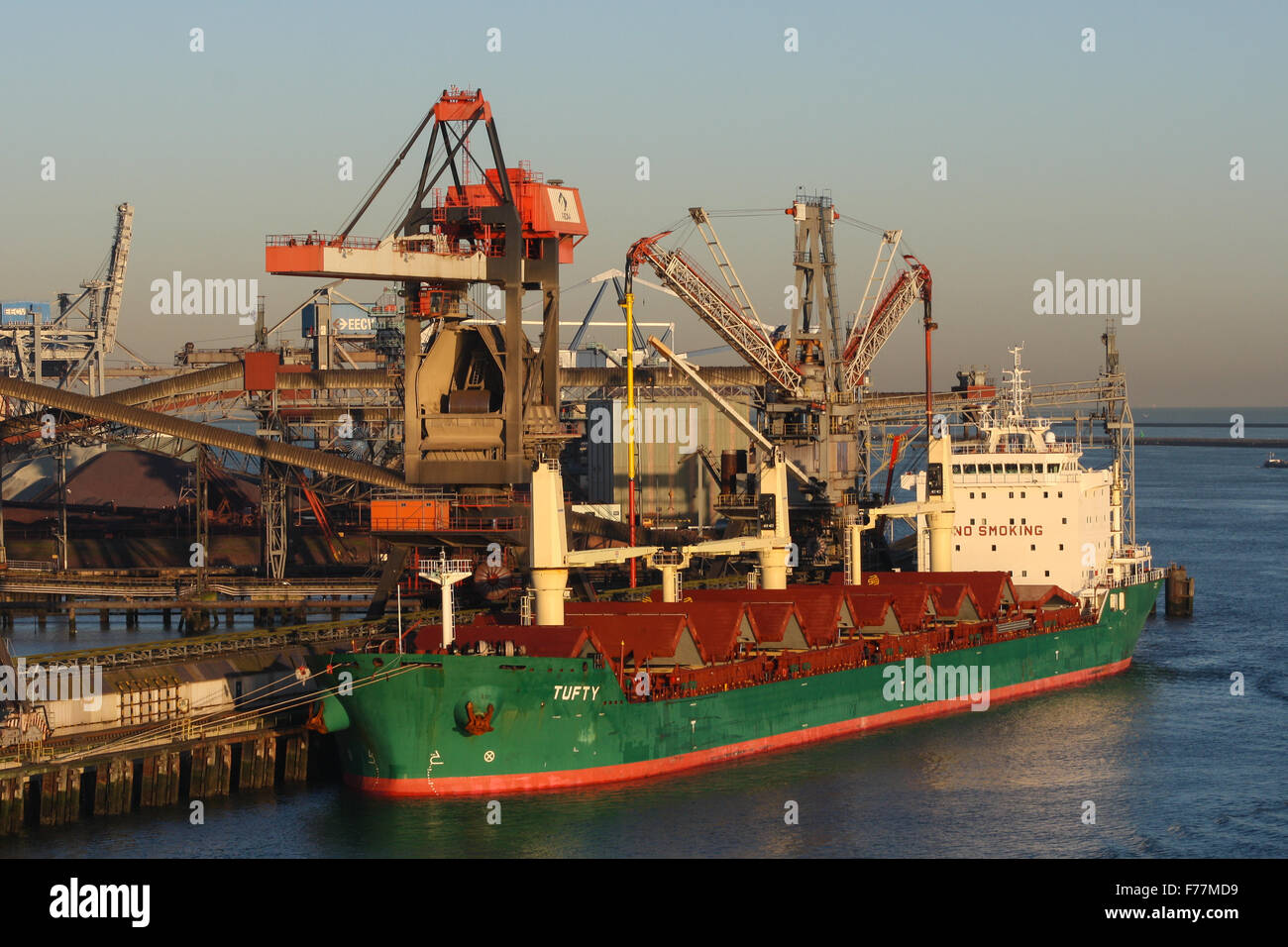 North Sea, Tufty, bulk carrier in Rotterdam harbour at sunrise with shipping, bulk containers tugs - Stock Image