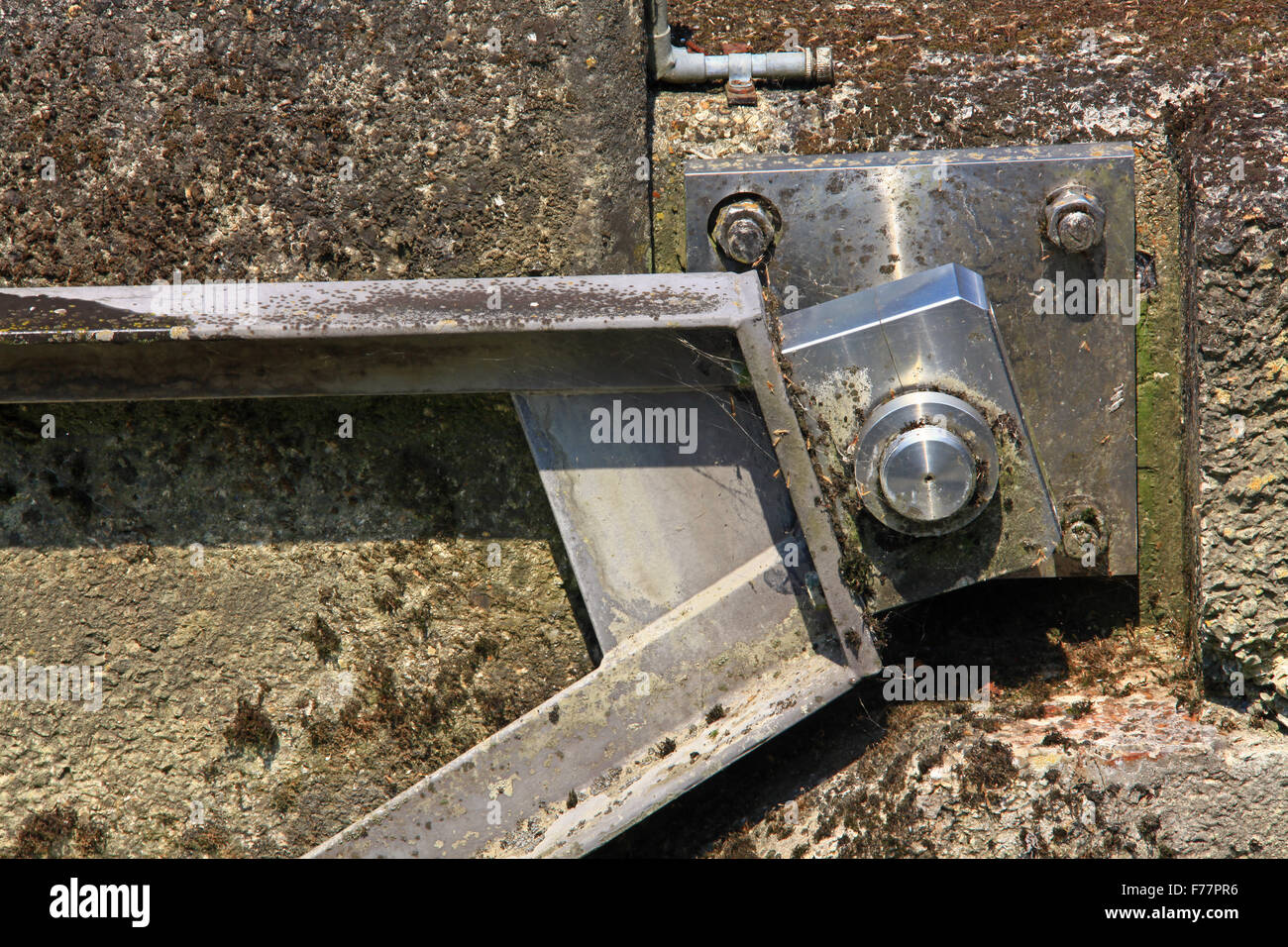 A stainless steel arm pivoting on a hinge pin secured to a concrete wall in an aquatic environment. - Stock Image