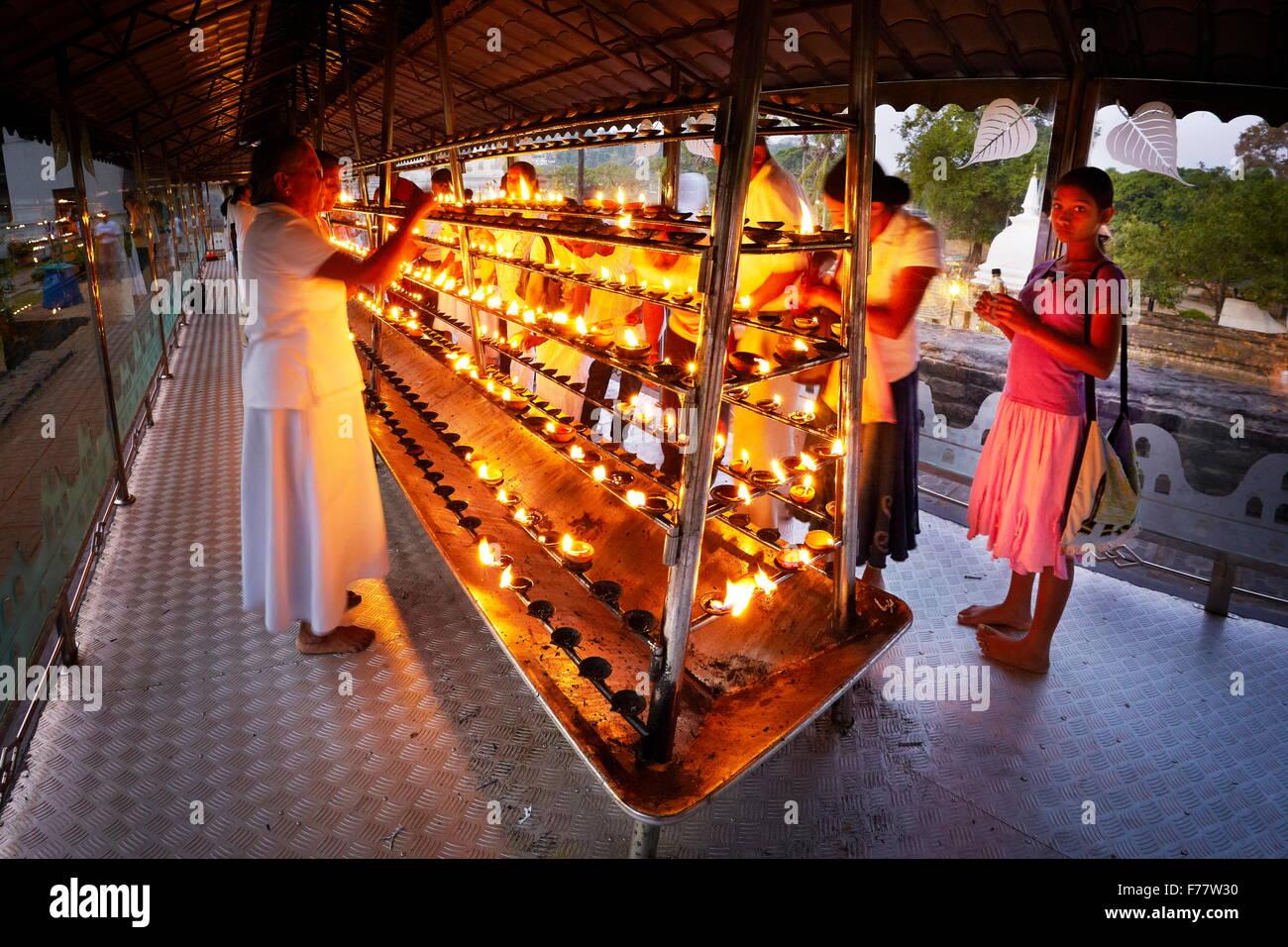 Sri Lanka, Kandy -  pilgrims light up candles in the Temple of the Tooth, Sri Dalada Maligawa, UNESCO World Heritage Site Stock Photo