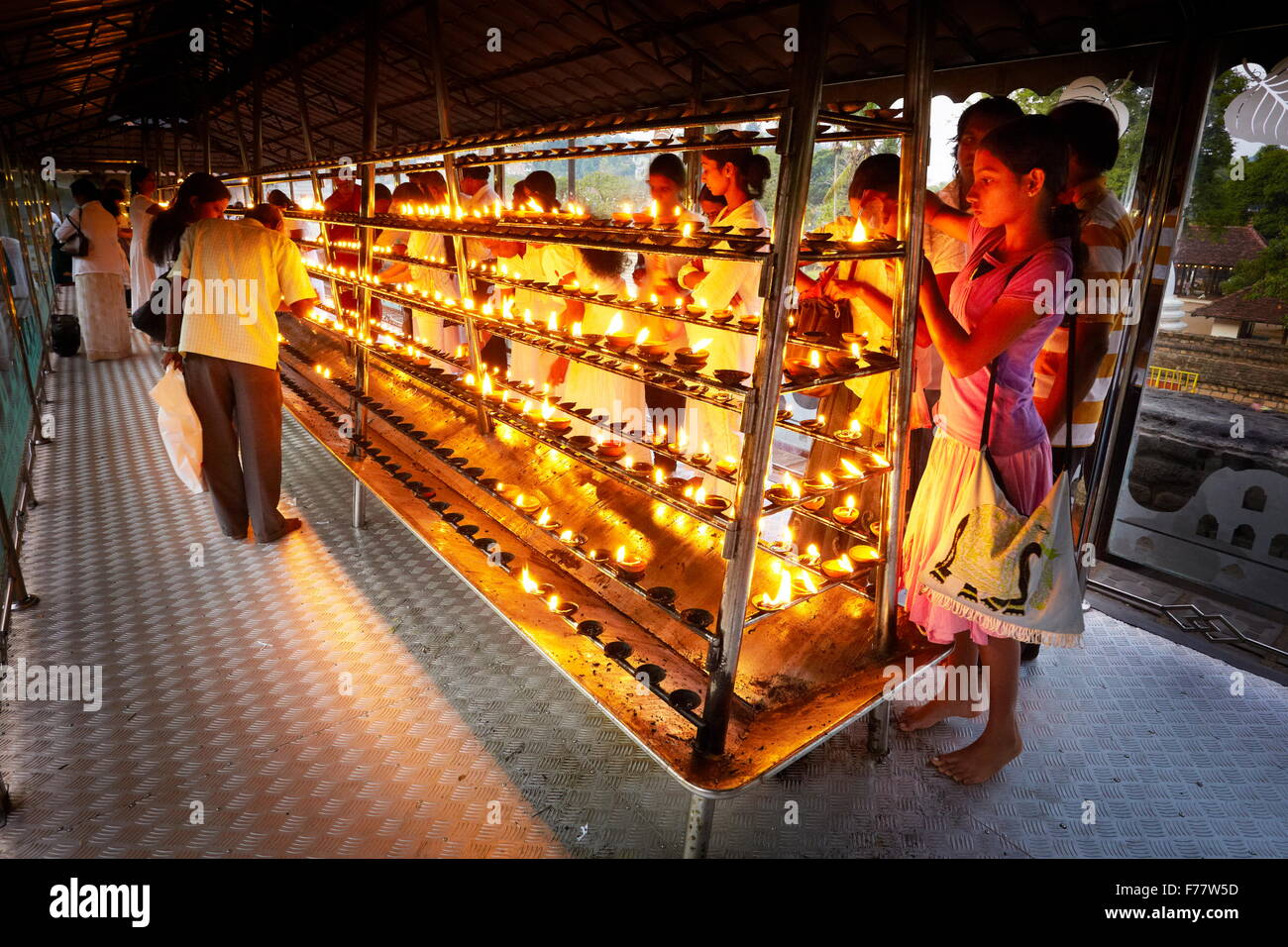 Sri Lanka, Kandy - pilgrims light up candles in the Temple of the Tooth, Sri Dalada Maligawa, Buddhist shrine, UNESCO Stock Photo