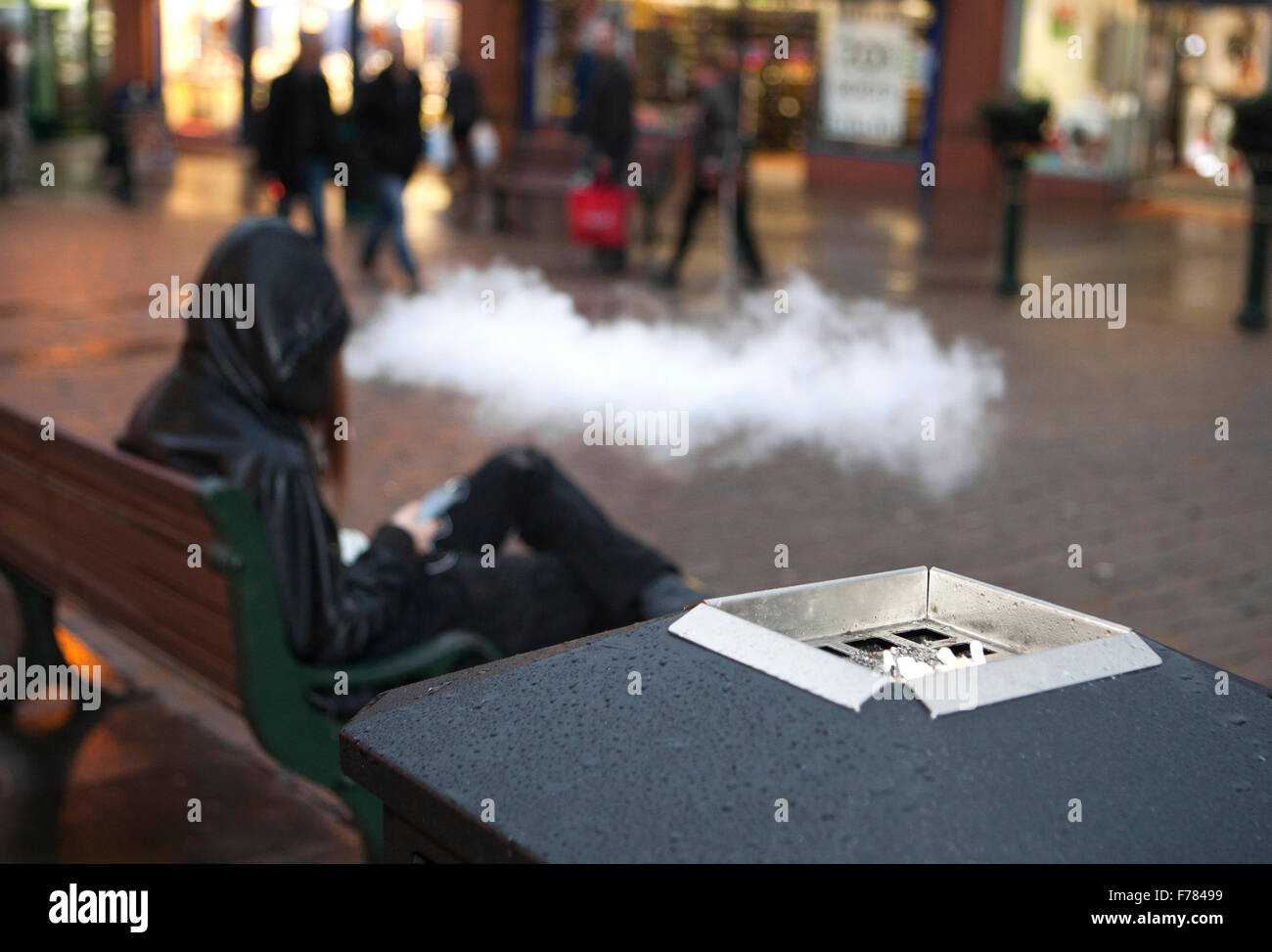 Large cloud of vapour issued by seated man smoking an e-cigarette in Oldham, Lancashire, UK - Stock Image