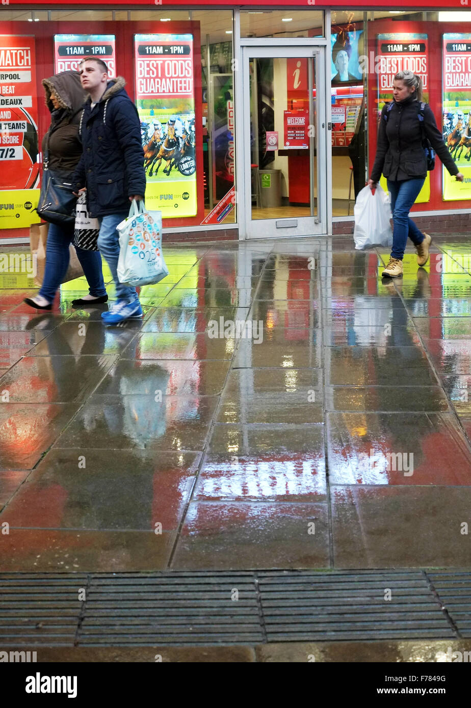 Shoppers walk on the reflective pavements after rainfall in Oldham, Lancashire, UK - Stock Image