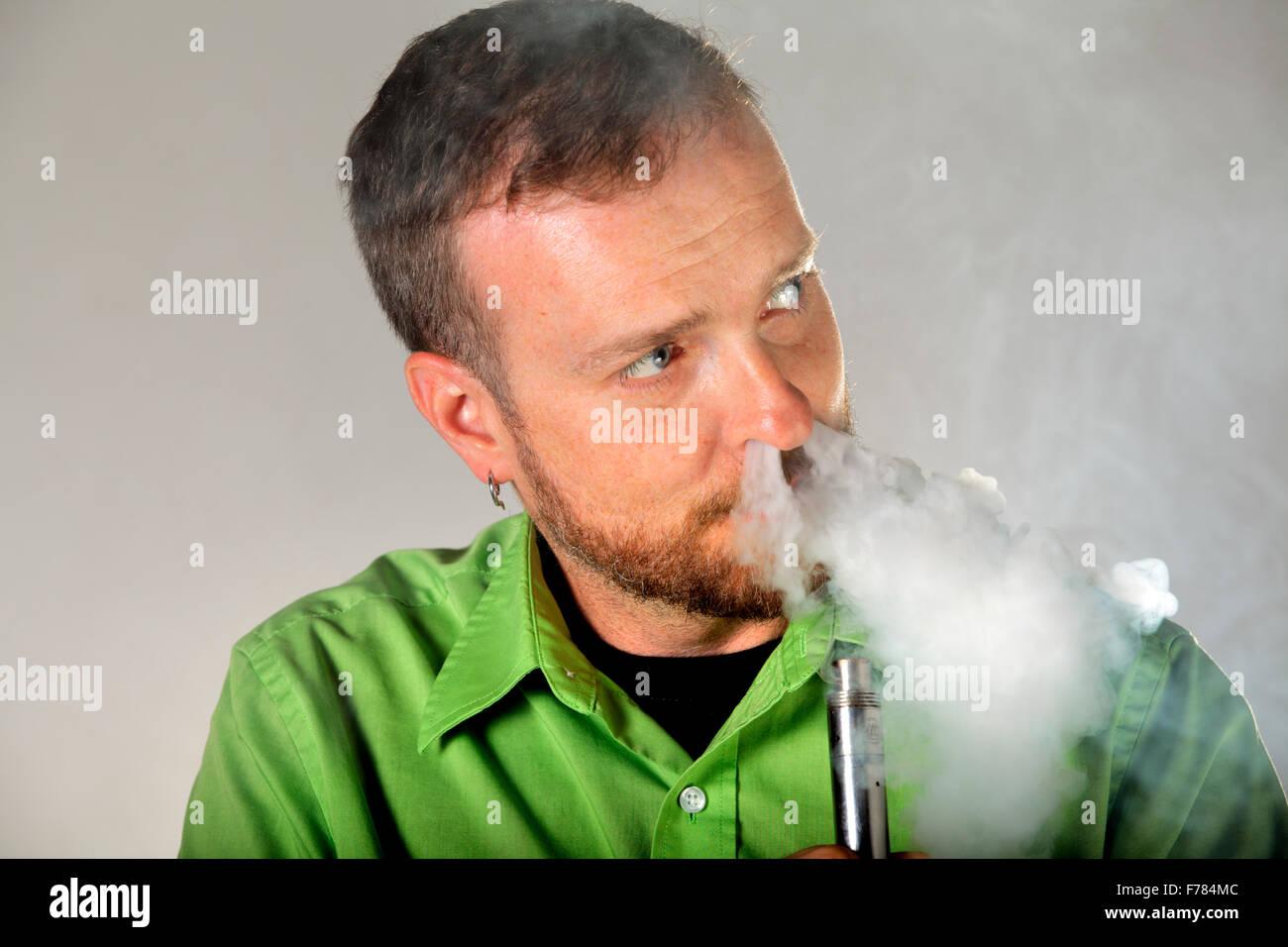 A man using a Tobh atty atomizer e-cigarette. - Stock Image