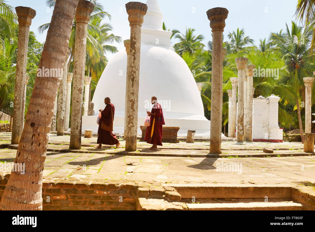 Sri Lanka - Mihintale Temple, monks in front of the stupa, Ambasthale Dagoba, UNESCO Stock Photo
