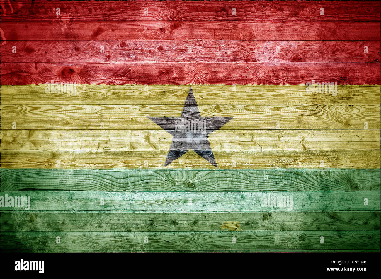 A vignetted background image of the flag of Ghana painted onto wooden boards of a wall or floor. - Stock Image