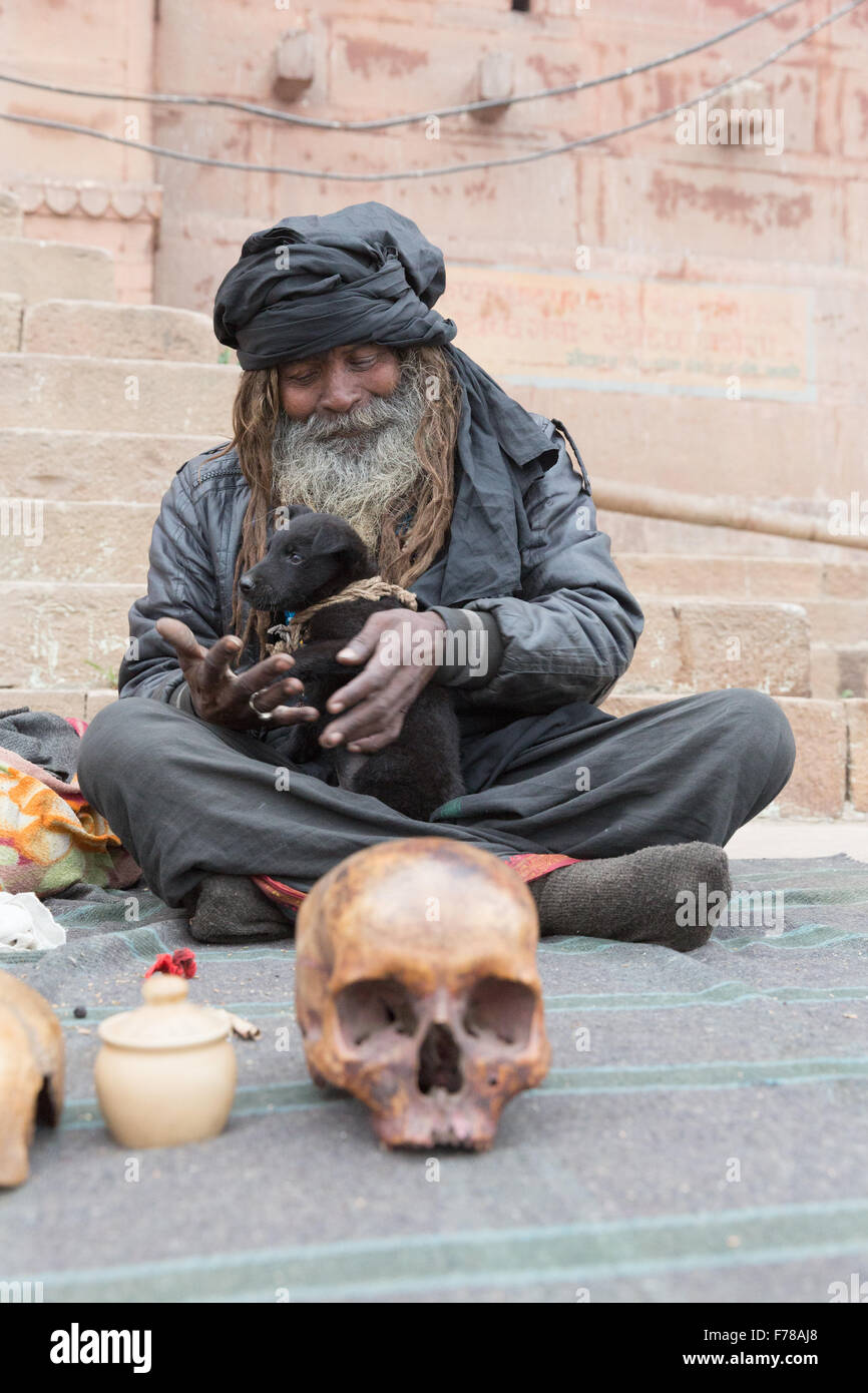 Black Bum Bum Baba, a holy Sadhu sits with his puppy and skull along the Ganges River in Varanasi. - Stock Image