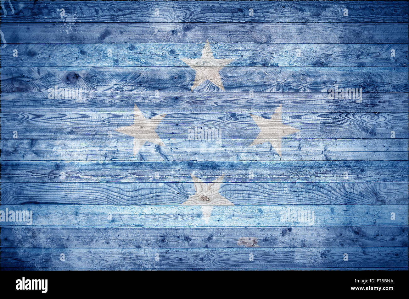A vignetted background image of the flag of Micronesia painted onto wooden boards of a wall or floor. - Stock Image
