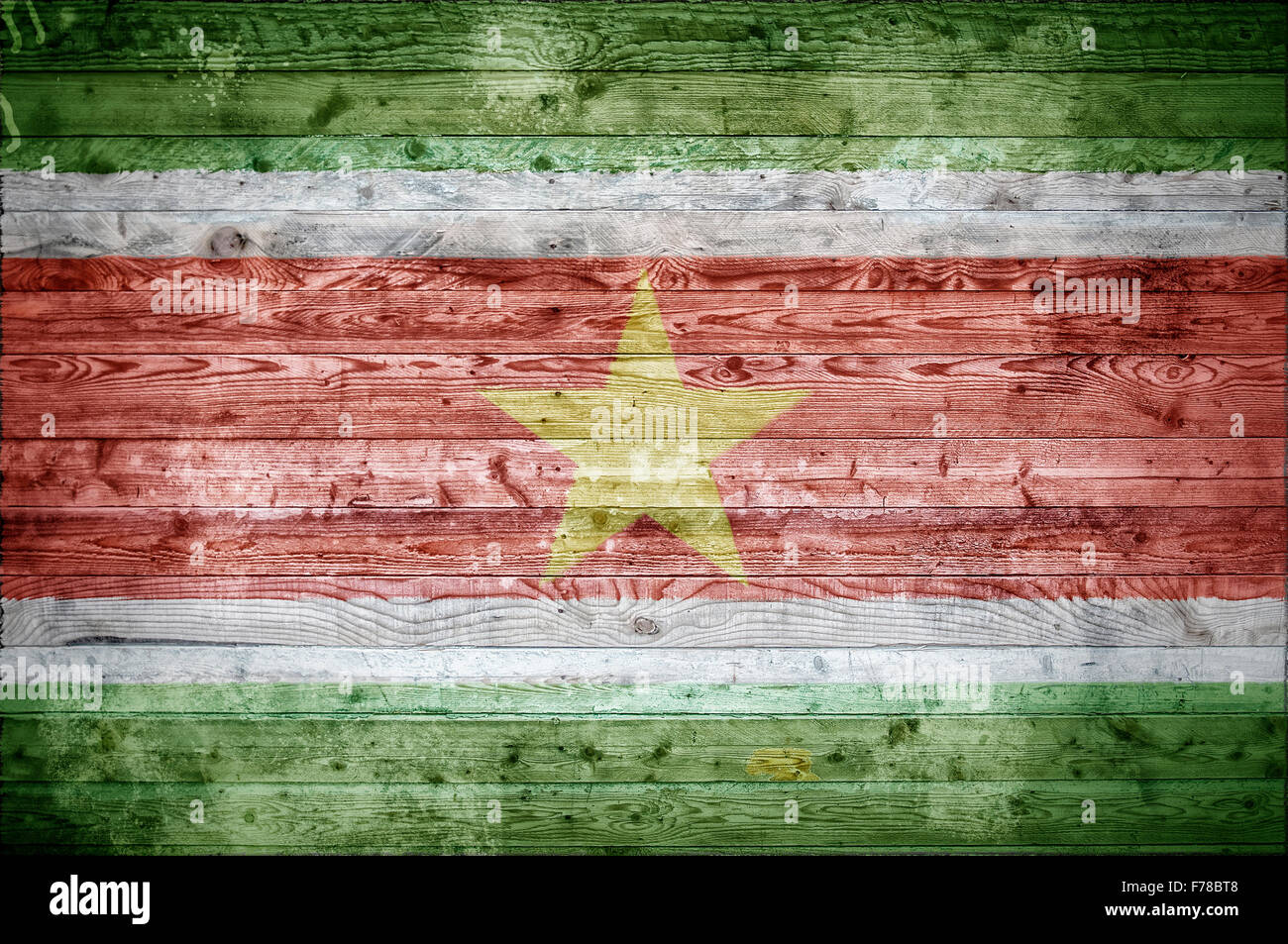 A vignetted background image of the flag of Suriname onto wooden boards of a wall or floor. - Stock Image