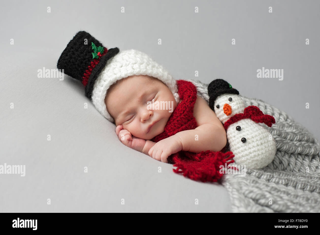Sleeping, two week old, newborn, baby boy wearing a crocheted snowman bonnet  and scarf with matching plush toy. daa4c52850a
