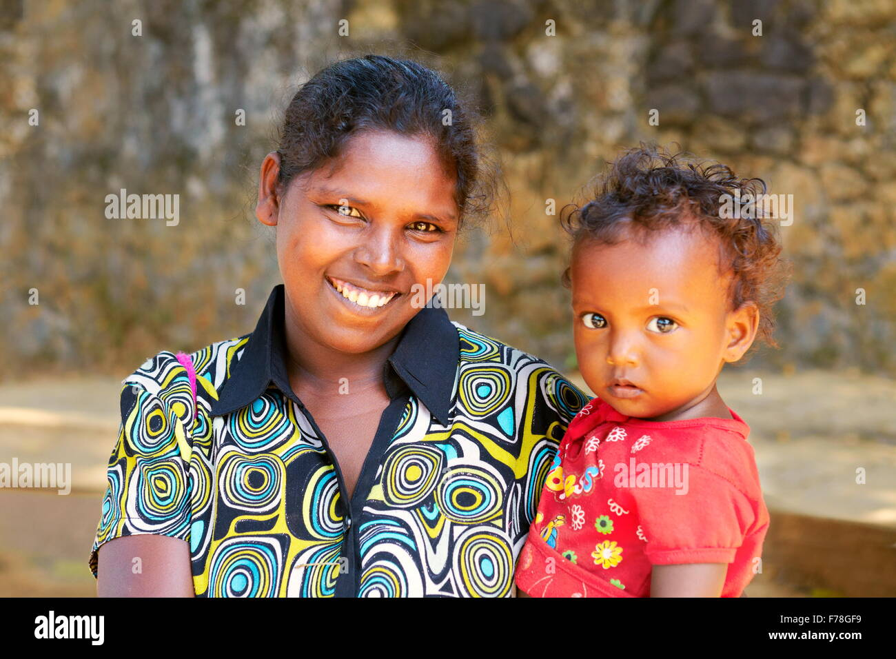 Sri Lanka – portrait of Sri Lankan young smiling woman with her baby child - Stock Image
