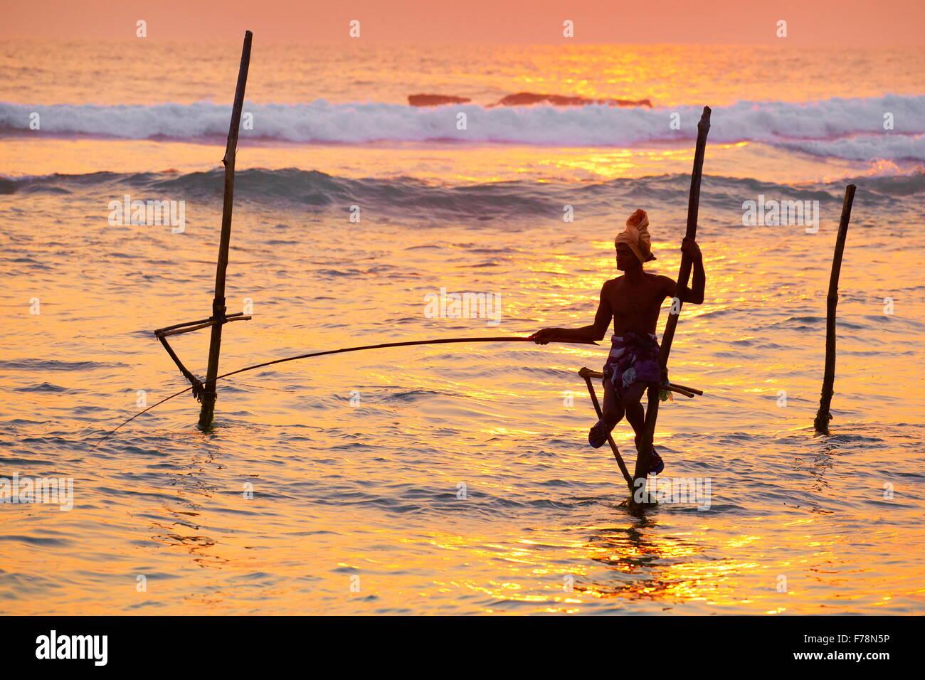Tropical sea landscape with stilt fisherman at sunset time, Koggala Beach, Sri Lanka, Asia - Stock Image