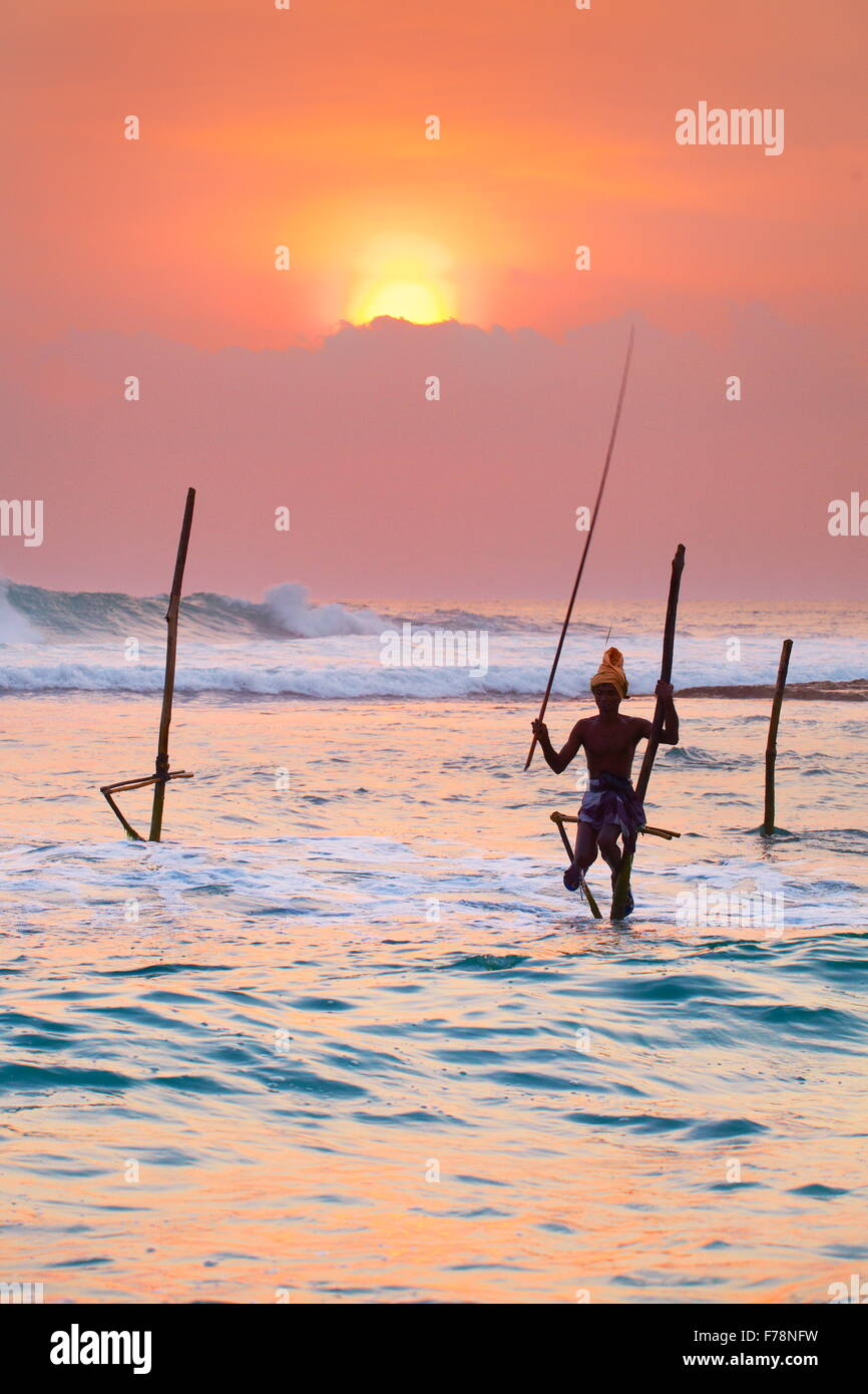 Local stilt fisherman at sunset, Koggala Beach, Sri Lanka, Asia - Stock Image