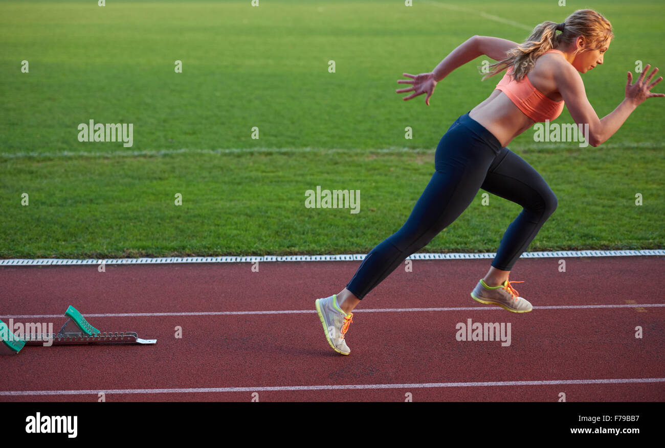 Woman Sprinter Leaving Starting Blocks On The Athletic Track Side View Exploding Start