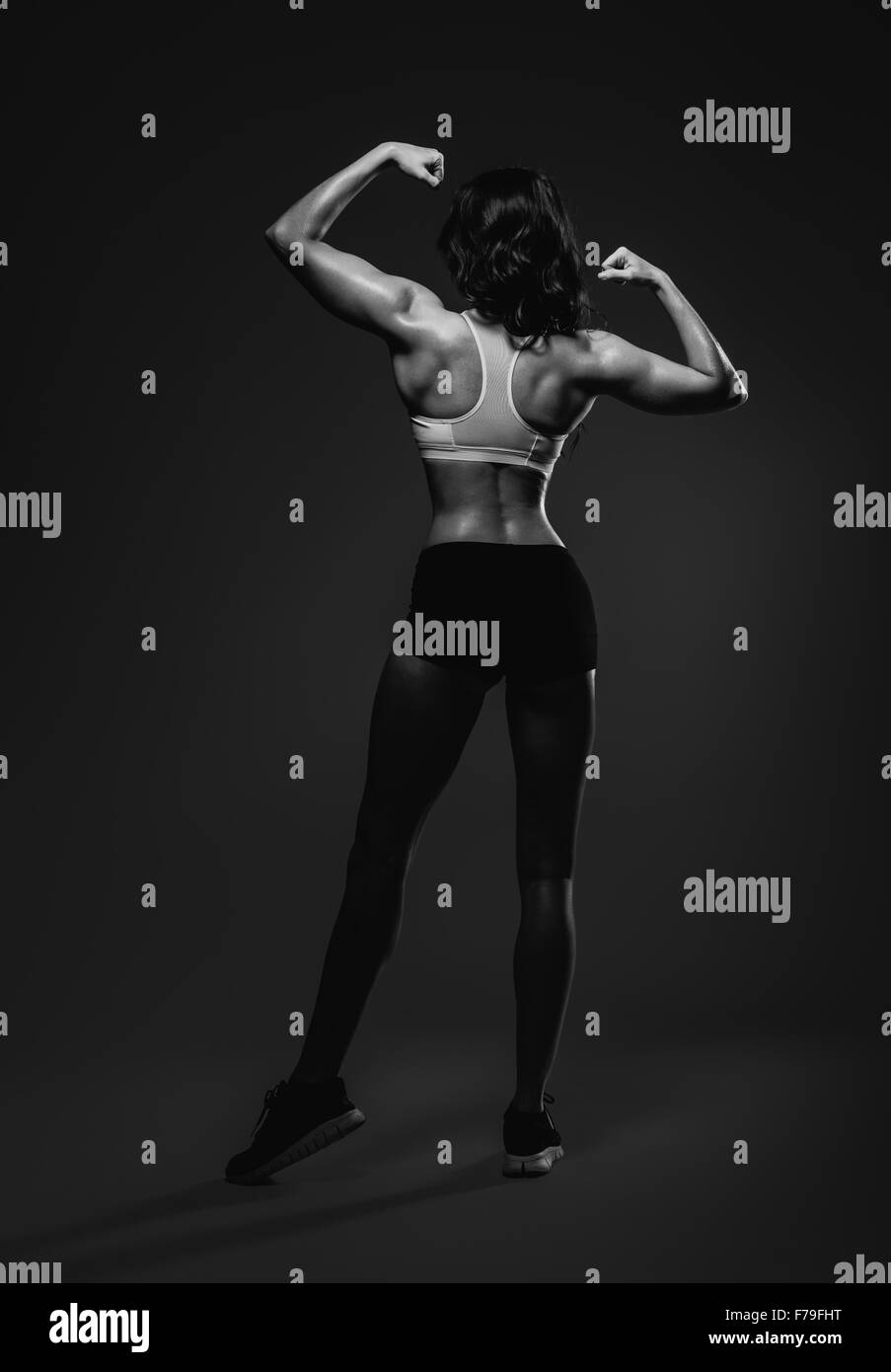 Athletic woman showing back and biceps muscles. Full length, studio shot - Stock Image