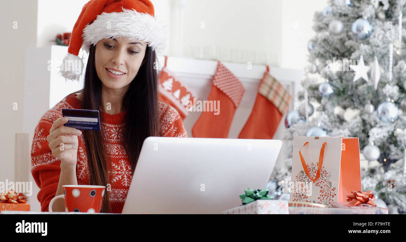 Smiling woman doing online Christmas shopping - Stock Image