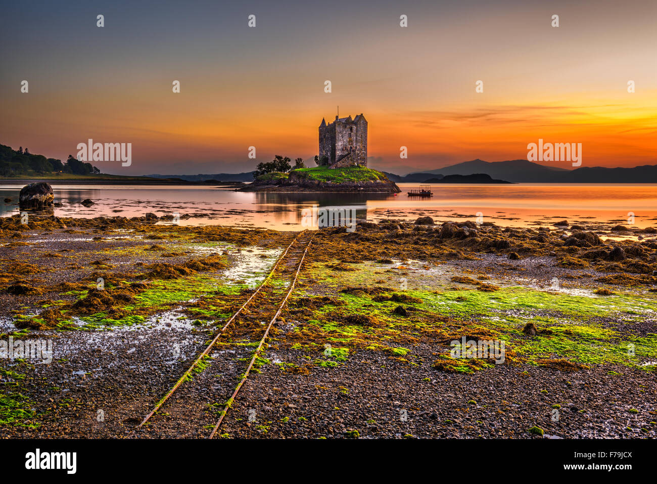 Sunset over Castle Stalker, Highlands, Scotland, United Kingdom. Long exposure and hdr processed. - Stock Image