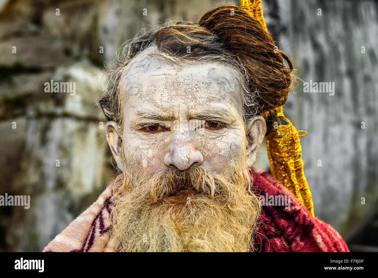Portrait of wandering  Shaiva sadhu (holy man) with traditional face painting in ancient Pashupatinath Temple - Stock Image