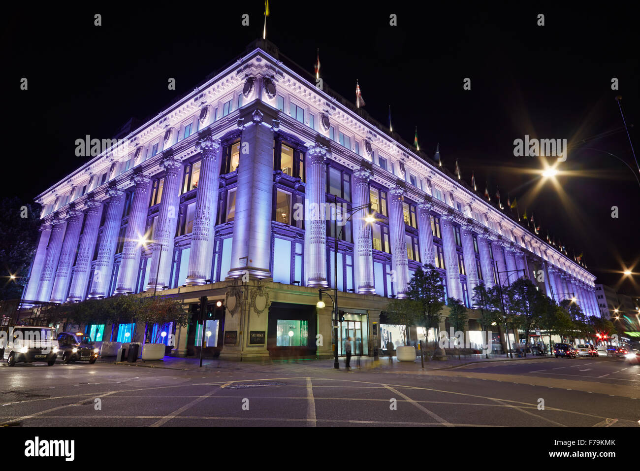 Selfridges Department Store in Oxford Street illuminated at night with people passing, central London - Stock Image