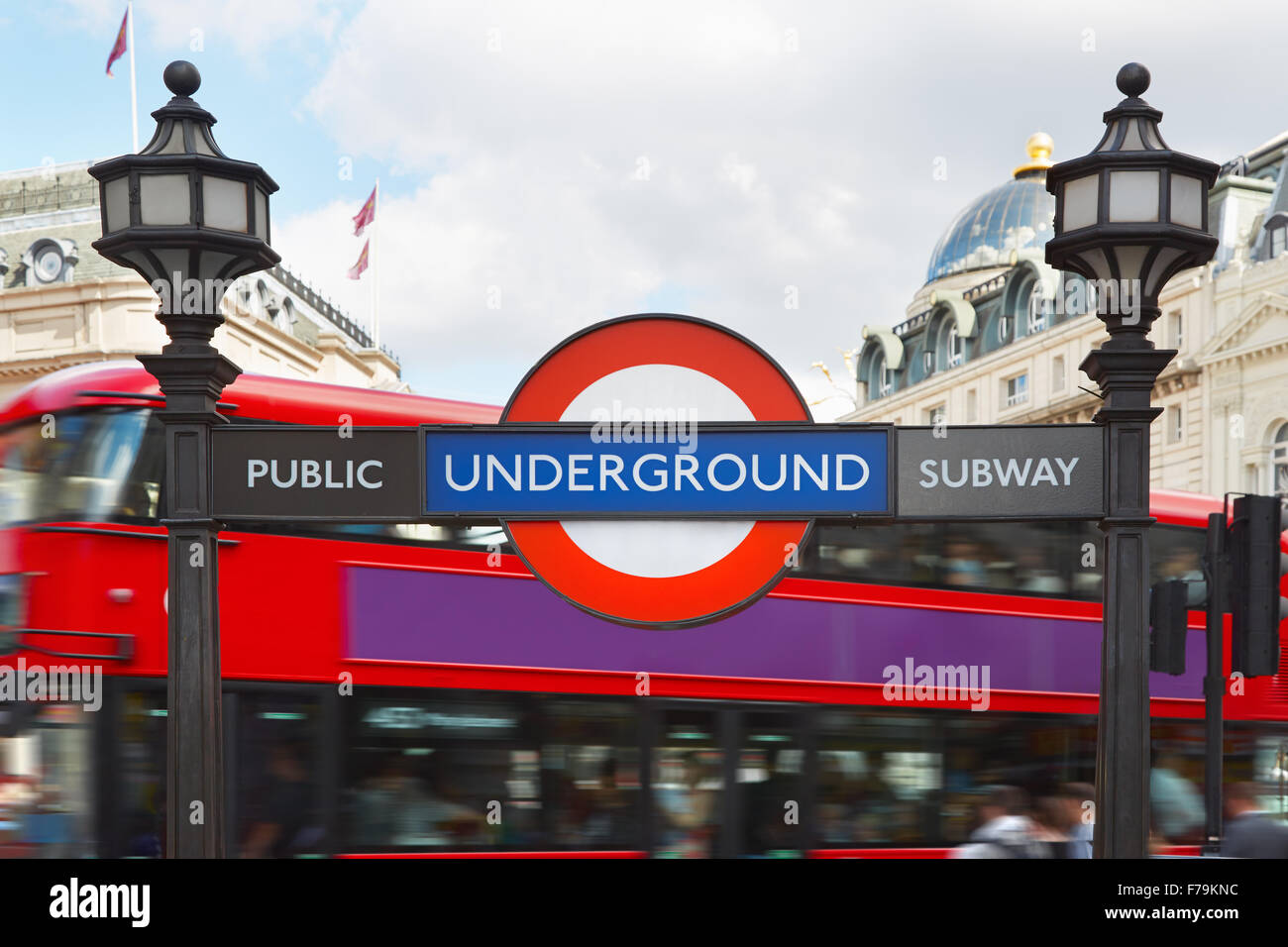 London underground sign with street lamps and red double decker bus background - Stock Image